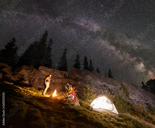 Fototapeta Night summer camping in mountains. Young couple hikers having a rest together beside bonfire and glowing tourist tent under starry sky full of stars and Milky way. On background big boulder and trees. obraz na płótnie