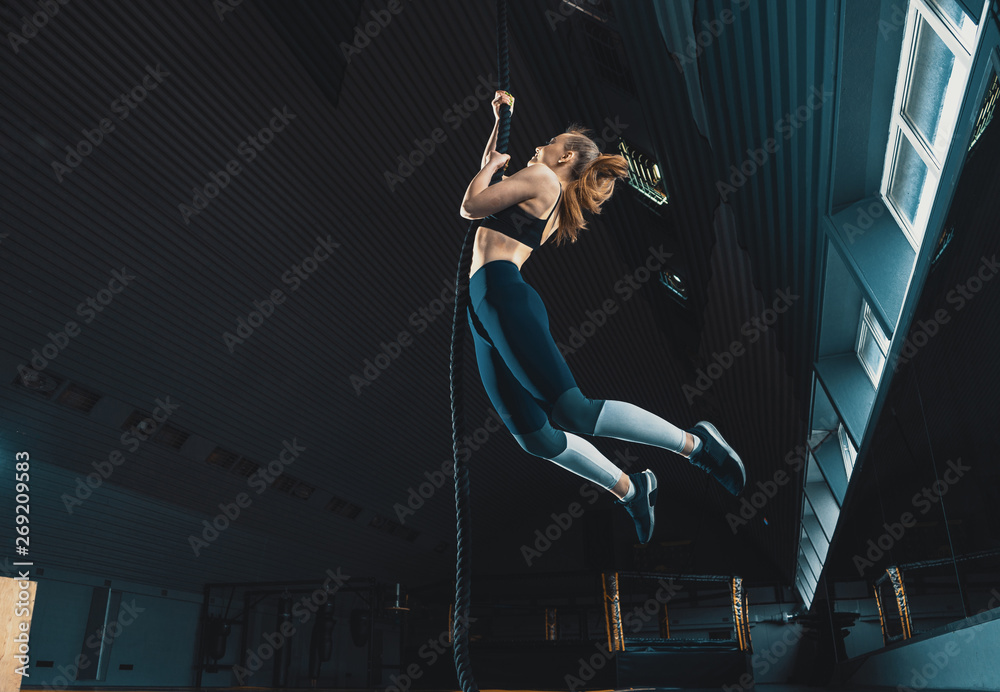 Fototapety, obrazy: Full length wide angle shot of a woman performing rope climbs at the gym.  Copyspace background with athletics healthy composition. Crossfit and fitness