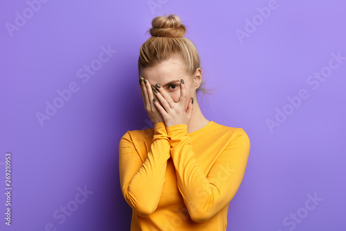Stressed scared woman covering her face with palm, feeling