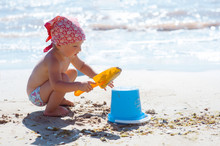 Kid Girl Play On A Beach. Child Building Sand Castle On Beach. Summer Water Fun For Family. Girl With Toy Buckets And Spade At The Sea Shore