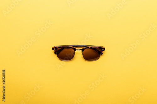 top view of trendy sunglasses on yellow background