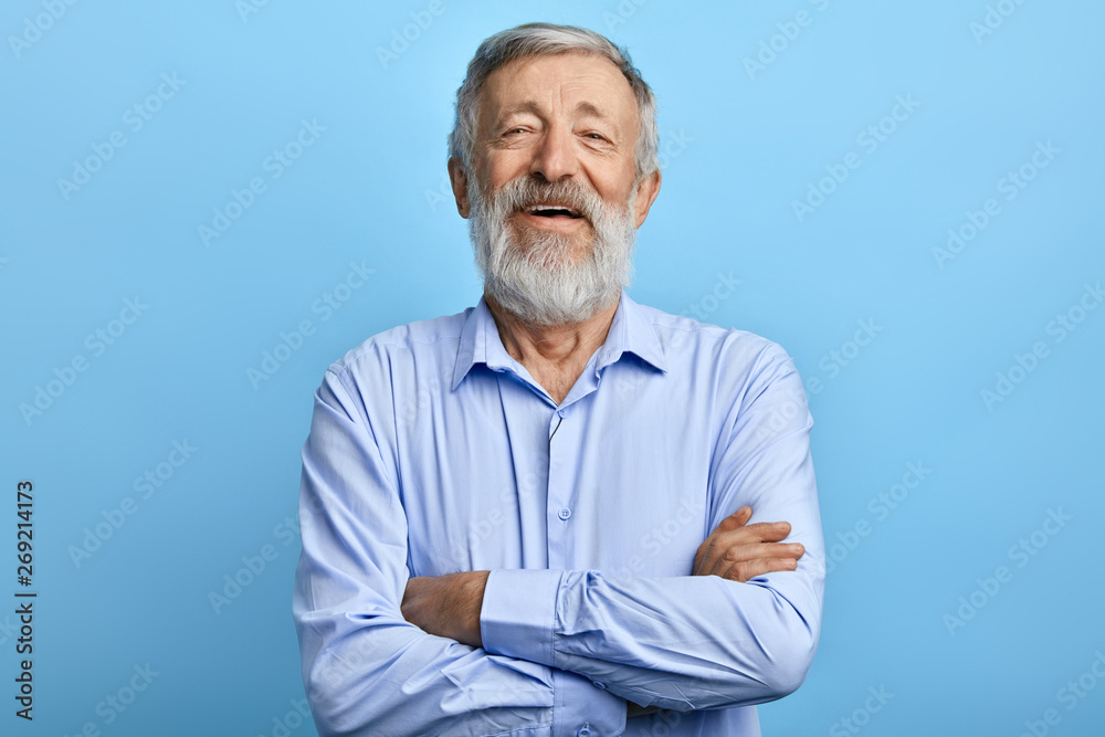 Fototapety, obrazy: friendly handsome man standing with crossed arms, laughing at something, looking at the camera. close up photo.happiness, feeling and emotion