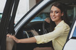 Young attractive dark haired woman smiling to the camera over her shoulder, sitting in a new automobile at the dealership. Beautiful woman buying new car at the salon, copy space
