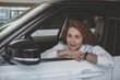 Young lovely woman sitting in a new automobile at the dealership, looking away dreamily. Beautiful woman looking relaxed, sitting in her new car, copy space. Purchase, retail concept