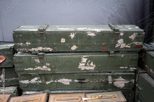 Photo  Stack of old military wooden box against grey background.