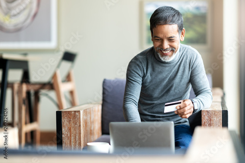 Fototapeta Attractive bearded hipster asian father or Hispanic old man using Laptop and credit card payment shopping online with customer network connection via omni channel system. Older man with technology. obraz