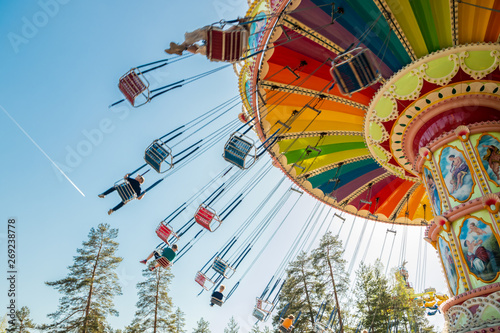 Poster Attraction parc Kouvola, Finland - 18 May 2019: Ride Swing Carousel in motion in amusement park Tykkimaki and aircraft trail in sky.