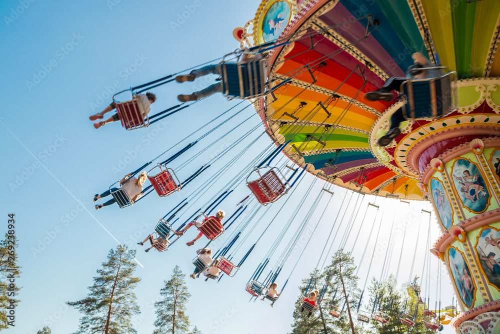 Fototapety, obrazy: Kouvola, Finland - 18 May 2019: Ride Swing Carousel in motion in amusement park Tykkimaki and aircraft trail in sky.