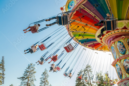 Obraz Kouvola, Finland - 18 May 2019: Ride Swing Carousel in motion in amusement park Tykkimaki and aircraft trail in sky. - fototapety do salonu
