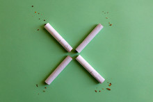 Two Broken Cigarettes Symbolizing Stop (X) Sign. Smoking Cessation Concept. Green Background.