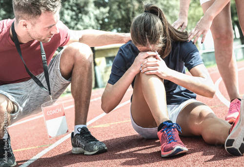 Fotomural Female athlete getting injured during athletic run training - Male coach taking