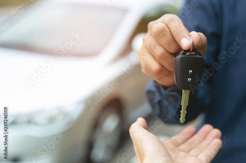 Obraz Car key, businessman handing over gives the car key to the other woman on car background. - fototapety do salonu