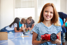 Portrait Of Female Student Building Robot Vehicle In After School Computer Coding Class