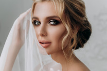 Bride With A Beautiful Hairstyle. Model Blonde In A Wedding Dress In White Interior