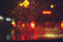 Drops Of Rain Drizzle On The Glass Windshield In The Night. Street In The Heavy Rain. Bokeh Tail Light. Soft Focus. Please Drive Carefully, Slippery Road. Soft Focus. Traffic Jam Car.