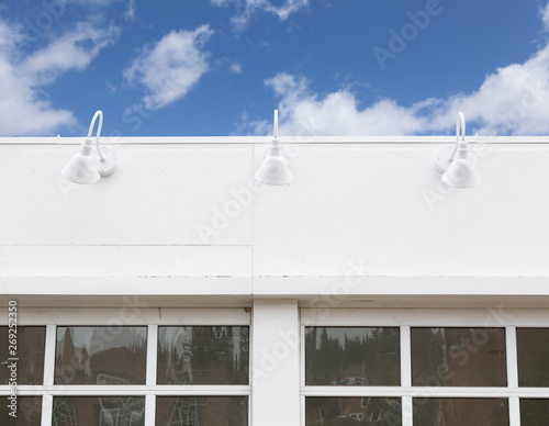Blank Building Front With Lamps and Windows Against Blue Sky