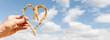 canvas print picture - Herz aus Ähren in einer Hand vor blauem Himmel