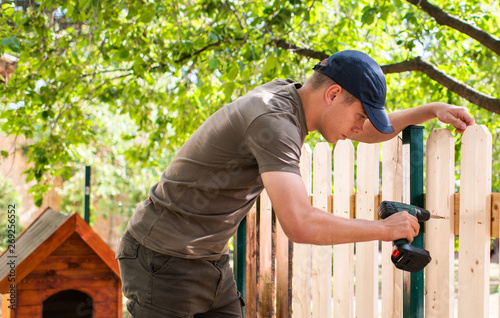 Obraz Young handsome man using electric cordless drill on wooden fence - fototapety do salonu