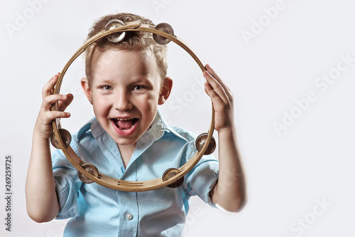 Photo  a cheerful boy in a blue shirt holding a tambourine and smiling on a light backg