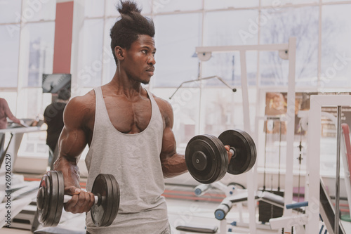 Handsome African sportsman looking focused, lifting heavy dumbbells at the gym Фотошпалери