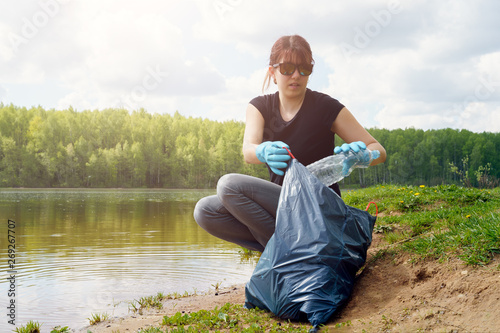 Photo of girl in rubber gloves with dirty plastic bottle in her hands on river b Canvas-taulu