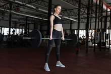 Young Woman Weight Lifting In Gym