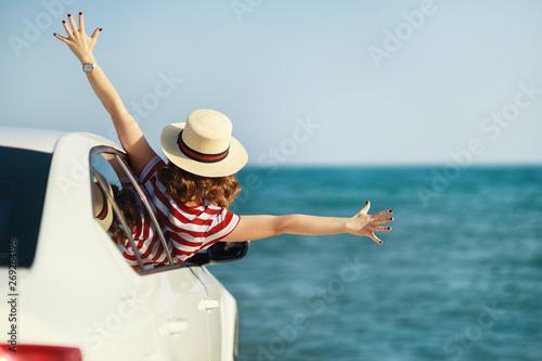 Fototapeta happy woman girl goes to summer travel trip in   car.