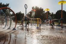Toddler Boy Playing With Water Toy At Splash Pad