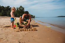 Toddler Boy And Dad Building Sand Castle At Beach