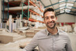 Young manager smiling while standing in a large warehouse