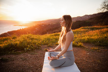 Side View Of Athlete Meditating While Sitting On Mountain During Sunset