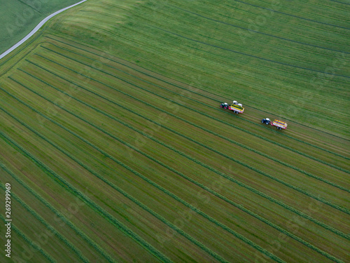 Aerial view of agriculture field with tractors harvesting hay