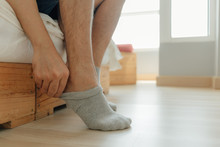 Man Is Wearing Socks Into His Feet In The Bedroom. Concept Of Getting Ready And Dress Up.