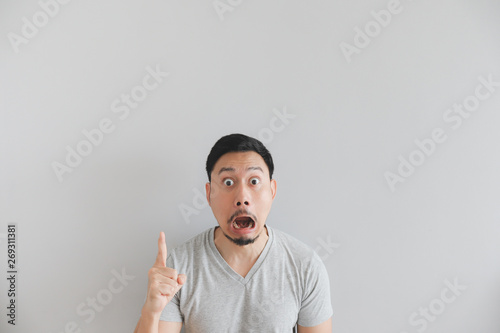 Fotografie, Obraz  Shocked face of man in grey t-shirt with hand point on empty space