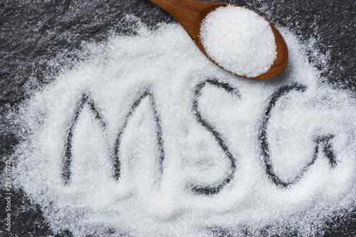 Fotografie, Obraz  Heap of monosodium glutamate on wooden spoon and dark background - text MSG