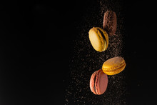 Colored Macaroons, French Cookies, Colored Levitates With Cocoa Powder On A Black Background