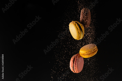 Obraz na plátně Colored macaroons, French cookies, colored levitates with cocoa powder on a blac