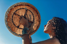 Beautiful Young Woman With Shaman Drum Outdoors And Playing Ethnical Music