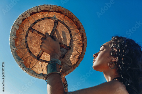 Canvastavla beautiful young woman with shaman drum outdoors and playing ethnical music