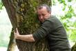 Leinwanddruck Bild - Portrait of man hugging a tree in a forest