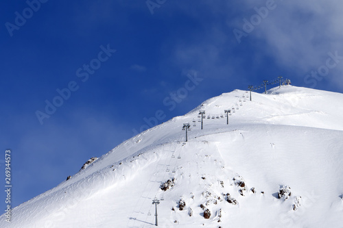 Snowy off-piste ski slope and ropeway at winter morning #269344573