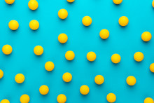 Many Balls For Table Tennis On Turquoise Blue Background. Flat Lay Image Of Many Yellow Ping-pong Balls
