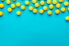 Many Balls For Table Tennis On Turquoise Blue Background. Flat Lay Image Of Many Yellow Table Tennis Balls With Copy Space. Minimalist Photo Of Yellow Ping-pong Equipment