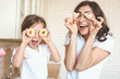 canvas print picture - Happy mother and daughter with tasty cookies having fun in kitchen at home
