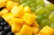 Tasty mango with berries and grapes, closeup