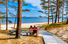 Happy Couple Of Seniors Are Resting And Looking At A Distance Near A Sandy Beach Of The Baltic Sea