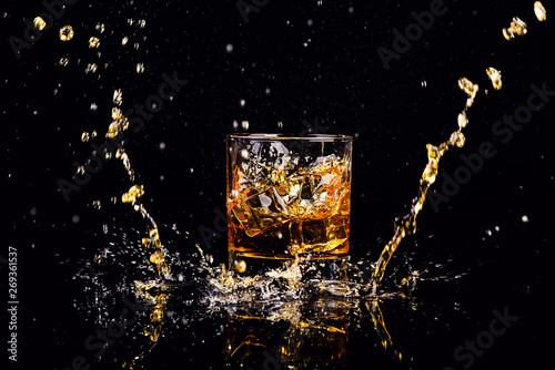 Fotografie, Obraz  Isolated shot of whiskey with splash on black background