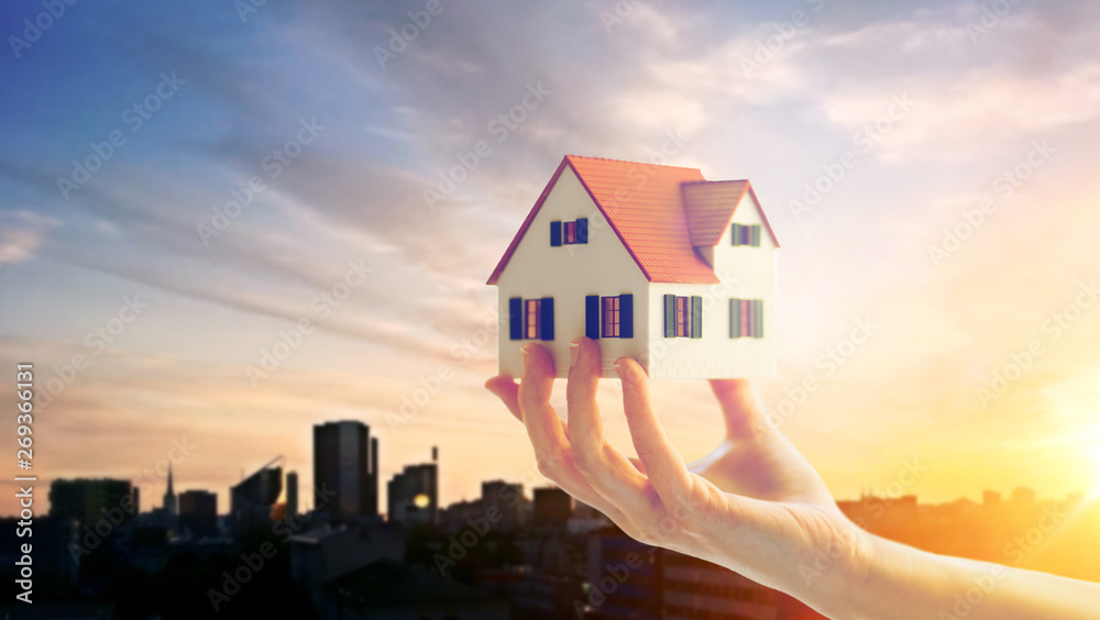 Fototapeta real estate, accommodation and property concept - close up of hand holding house or home model over sunset sky in tallinn city, estonia background