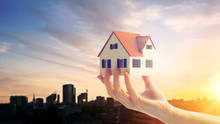 Real Estate, Accommodation And Property Concept - Close Up Of Hand Holding House Or Home Model Over Sunset Sky In Tallinn City, Estonia Background