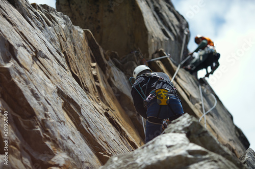 Abstract image of a two person rope of climbers on a rock tower. Fototapeta